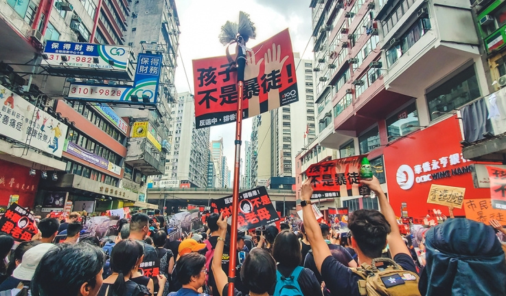 Protestors stand in a street in Hong Kong with signs.