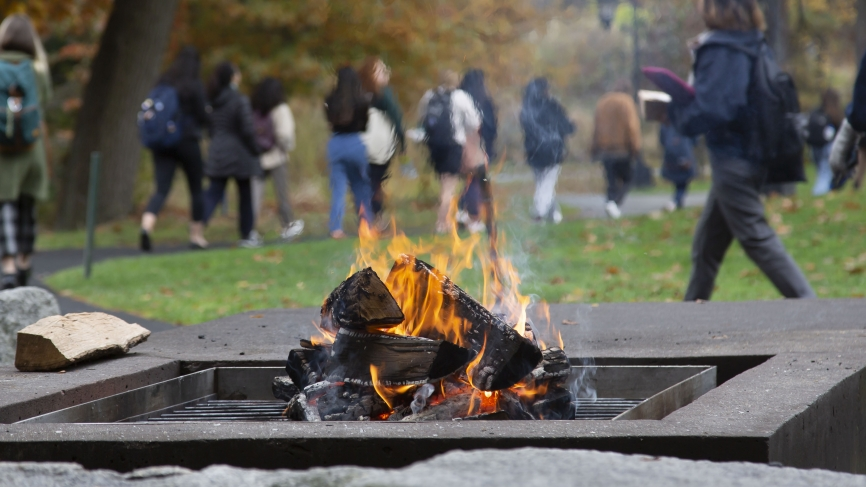 Students walk to lunch in Alumnae ballroom in the background. A fire pit is in the foreground.