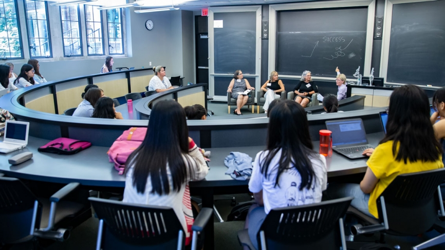 A panel of four women speaks to a crowded classroom.