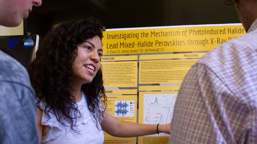 A student shows her poster to a group of people standing by