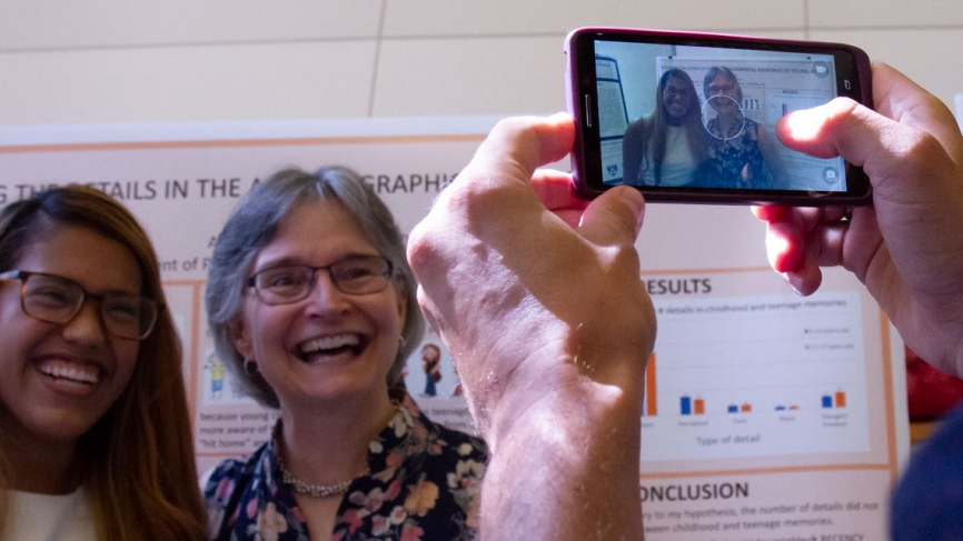 A student and her advisor take a photo with a smart phone