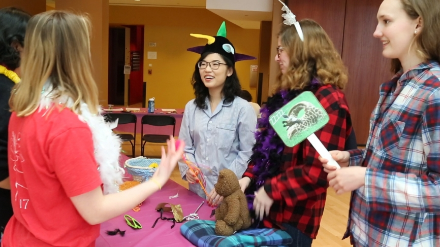 Students stand around a table with dress up props on it.