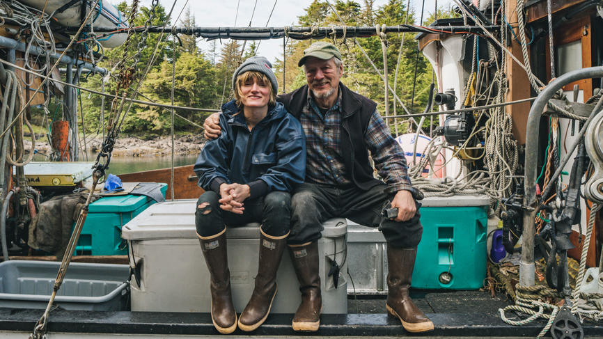 Elsa Sebastian and her father sitting on a fishing boat and smiling