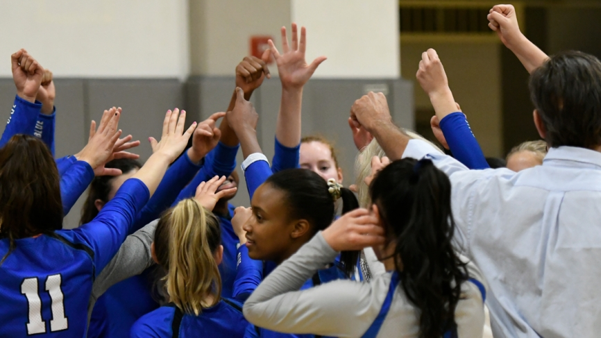 The Wellesley volleyball team stands with their hands up in a huddle.