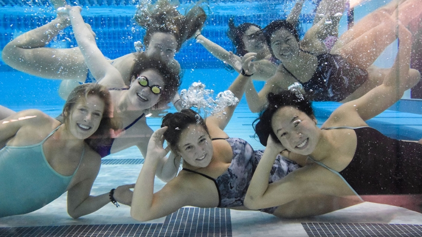 Swimmers pose underwater in a pool.
