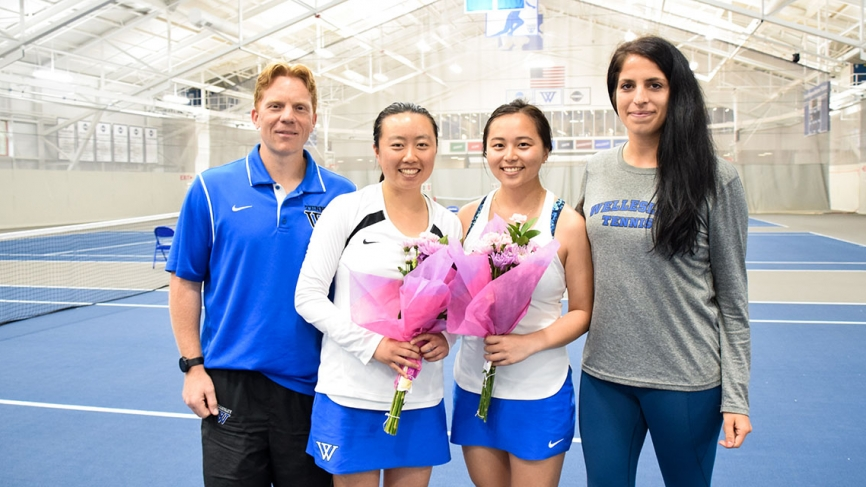 Two members of the tennis team pose with coaches on senior day