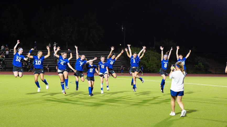 The Wellesley Field Hockey team jumps during a night game under the lights.