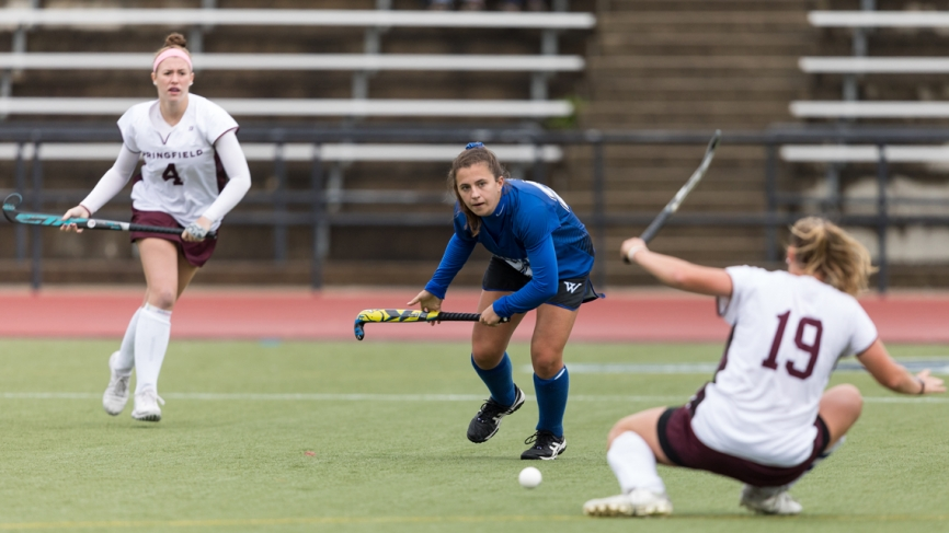 A Wellesley field hockey player prepares to pass a ball around two players from the opposite team.