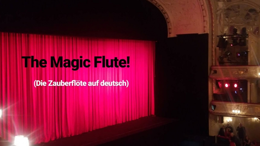 "The stage at the Berlin State Opera with a closed red curtain. Text reads, ""Magic Flute"" (Die Zauberflöte auf deutsch)"