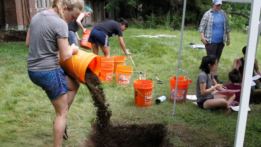 A student pours dirt into a hole from an orange utility bucket.