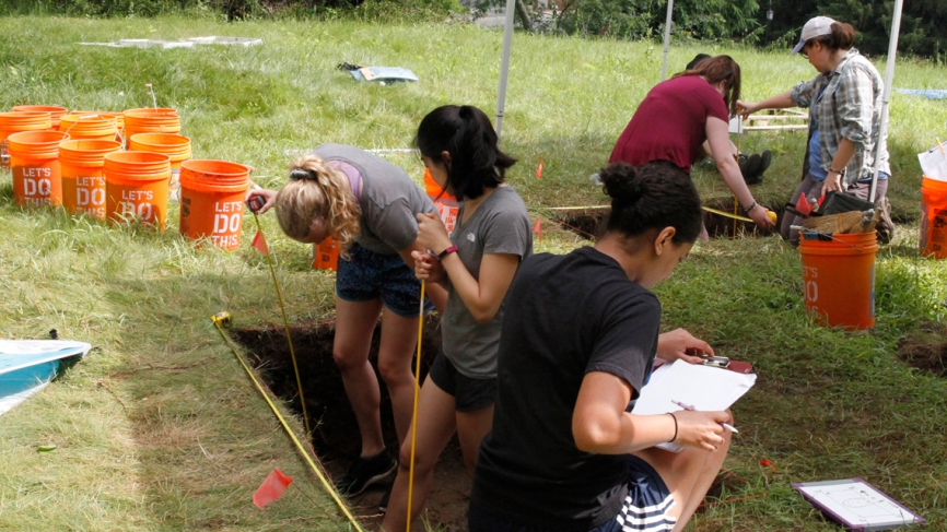 Students measure the dig site and record what they find in white notebooks.