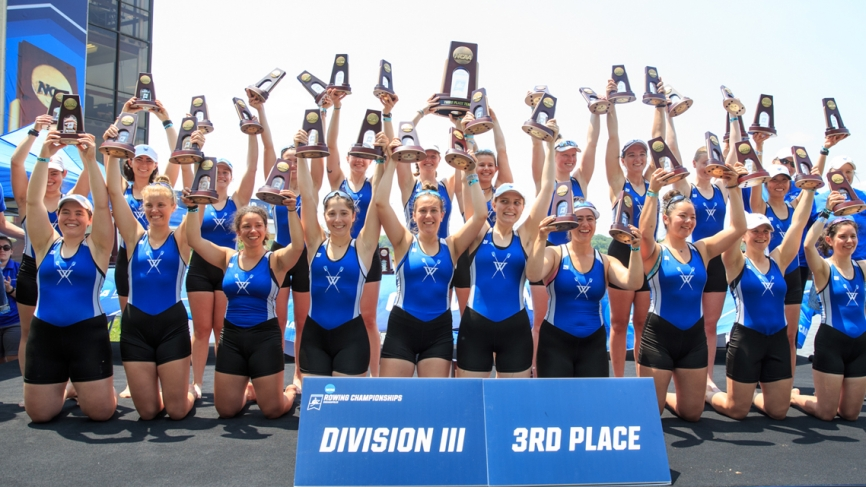 The Wellesley Blue crew team hold up trophies.