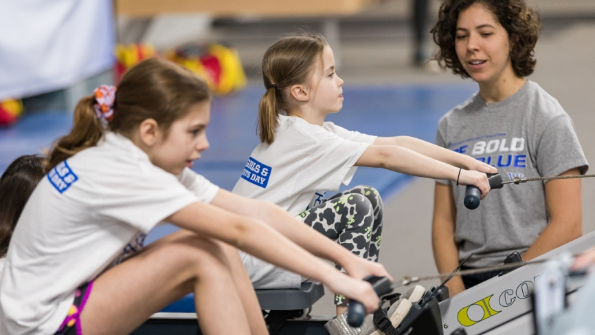 Two young girls sit on ergs as a Wellesley rower looks on