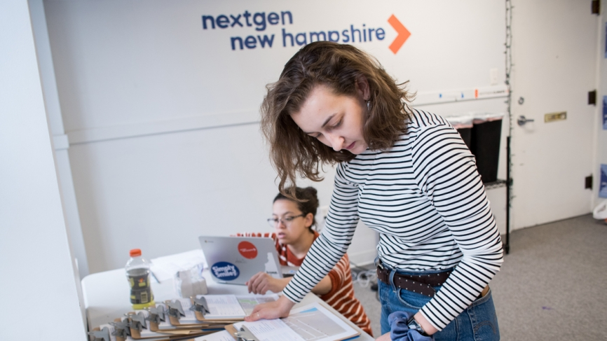 a woman looks down at a series of clipboards on a table. behind her a table reads, nextgen america