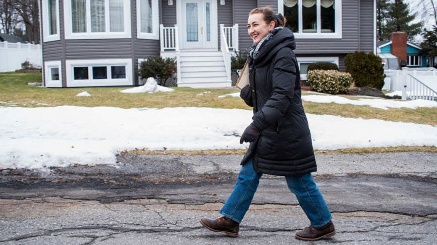 A woman walks down a snowy street in front of a gray house