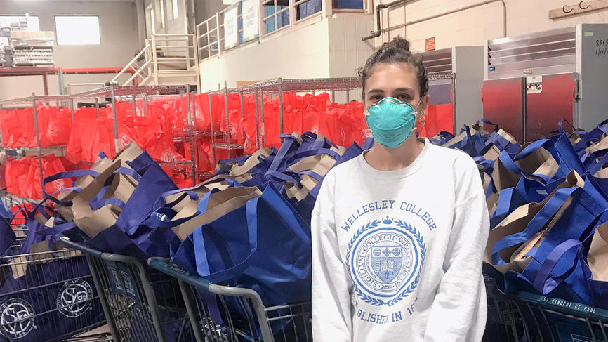 student wearing a mask standing in front of donation bags