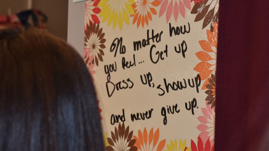"""A student looks at a sign on a wall that reads, """"No matter how you feel, get up, dress up, show up, and never give up."""""""
