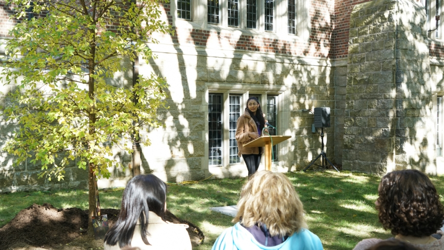 A student speaks at a podium next to a newly planted tree.
