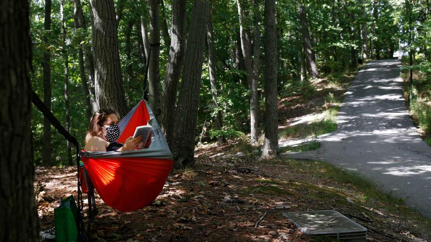 A student reading a book while sitting in a hammock