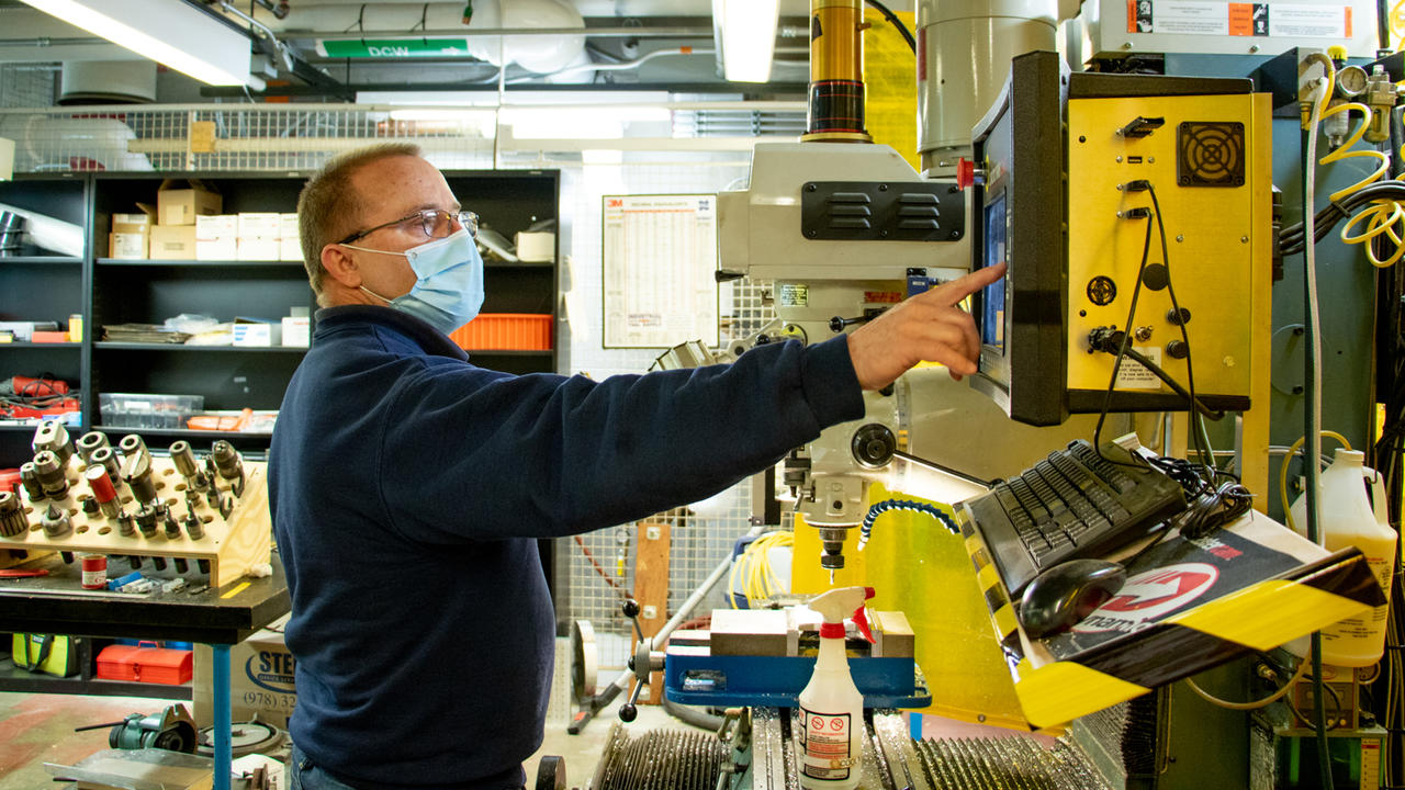 A photo of Larry Knowles working in the machine shop on campus.