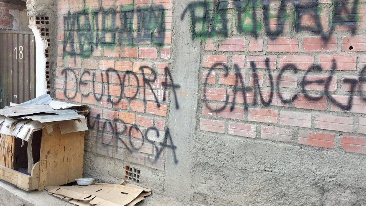 "Graffiti on the wall of a house, which reads ""Deudor moroso"""