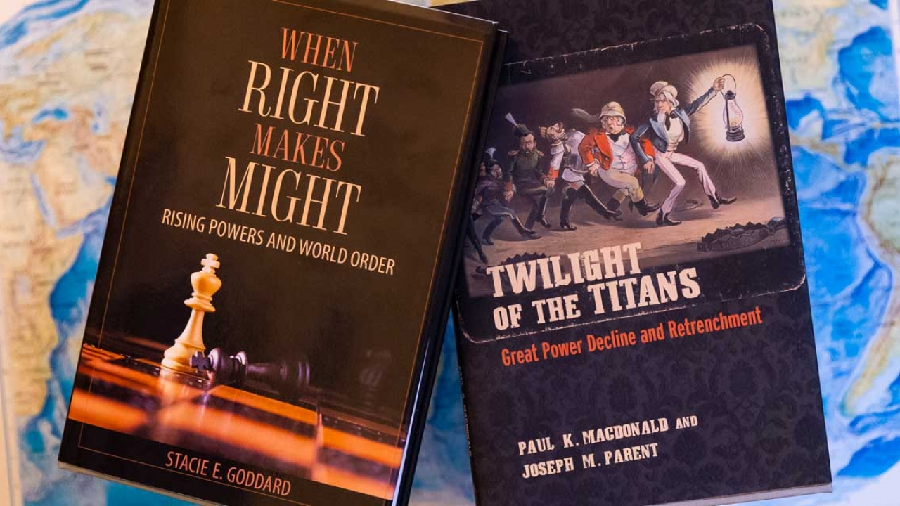 Two books appear on a map of the world. They read: When right makes might and twilight of the titans.