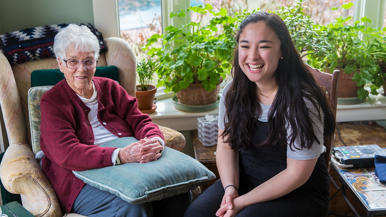 Kitty Gladstone sits with Wellesley student Margaret Calmer '18 in her home.