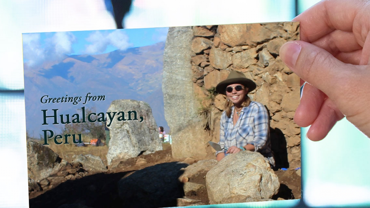 """A hand out of frame holds a postcard of a woman sitting at a dig site. It reads, """"Greetings from Hualcáyan, Peru."""""""