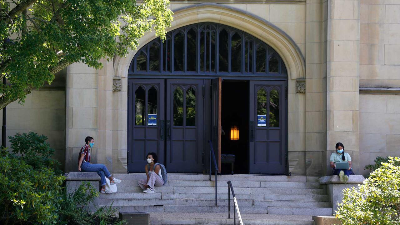 students socially distanced sitting on chapel steps