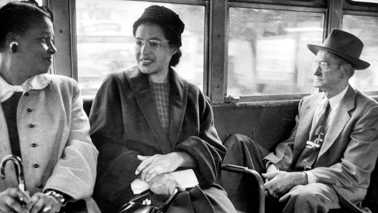 Rosa Parks (center) sits on a bus speaking to another woman.