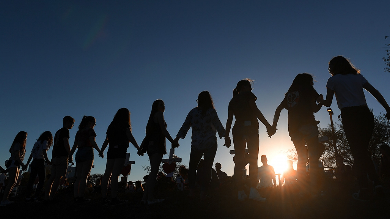 Students and their family members join hands outside Marjory Stoneman Douglas High School on February 18, 2018 in Parkland, FL.