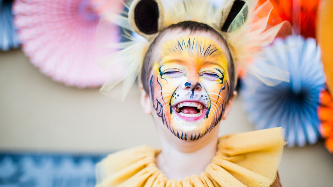 A child dressed up as a lion. He laughs.