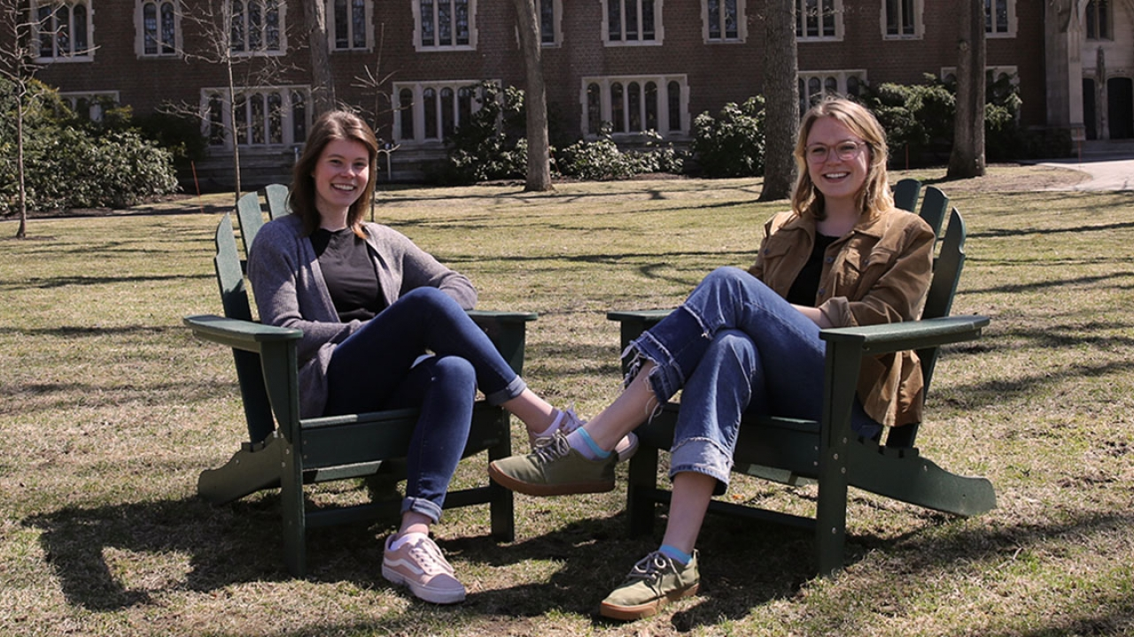 Two students sit in chairs in the academic quad.