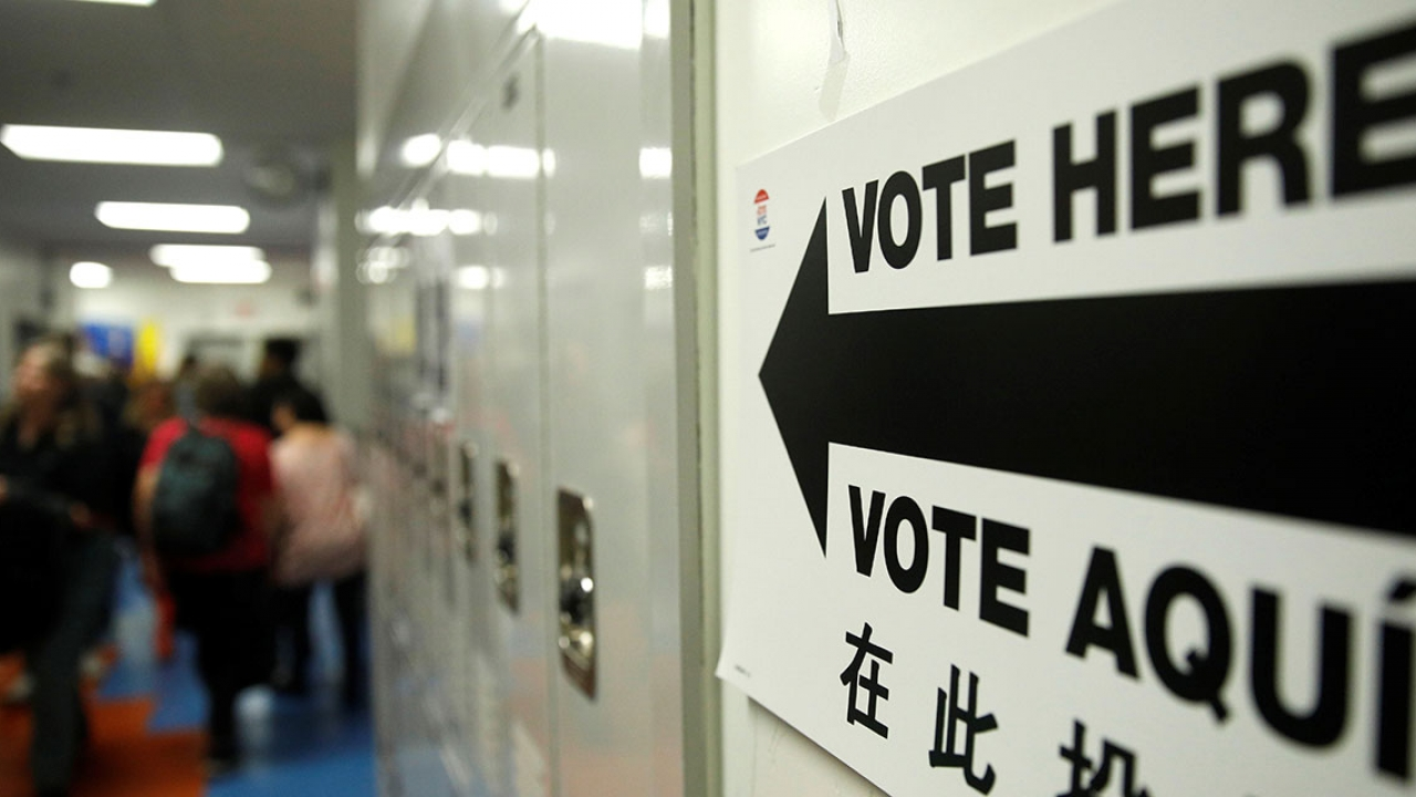 A sign on a wall by lockers reads Vote Here in English and Spanish