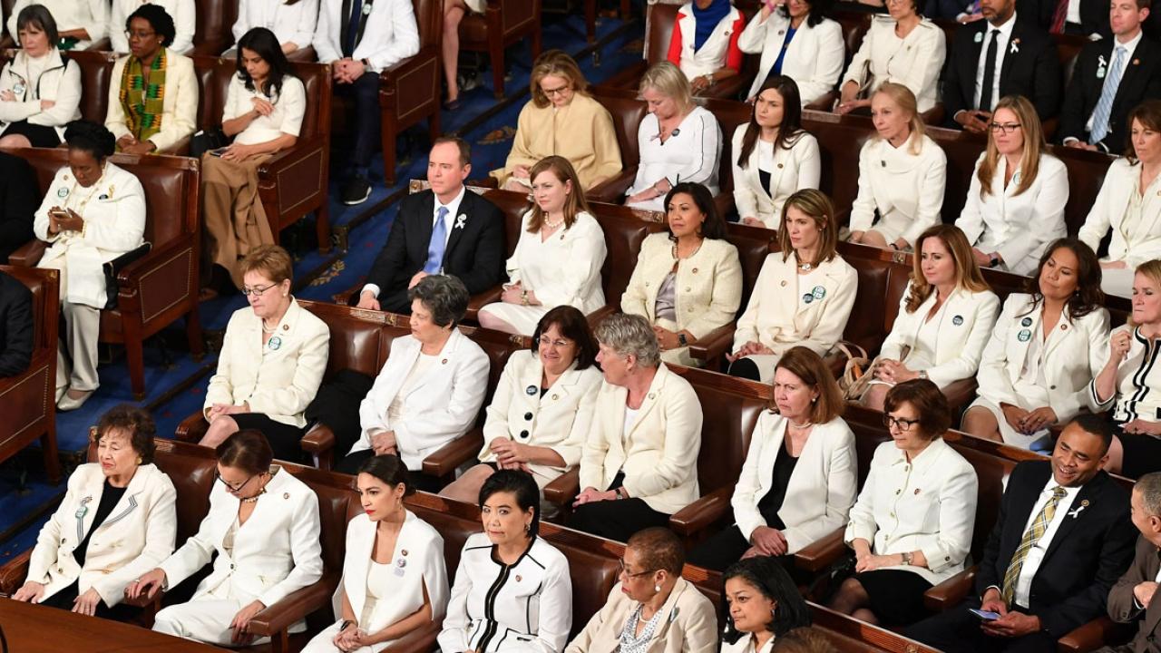 Women members of congress sit wearing white.