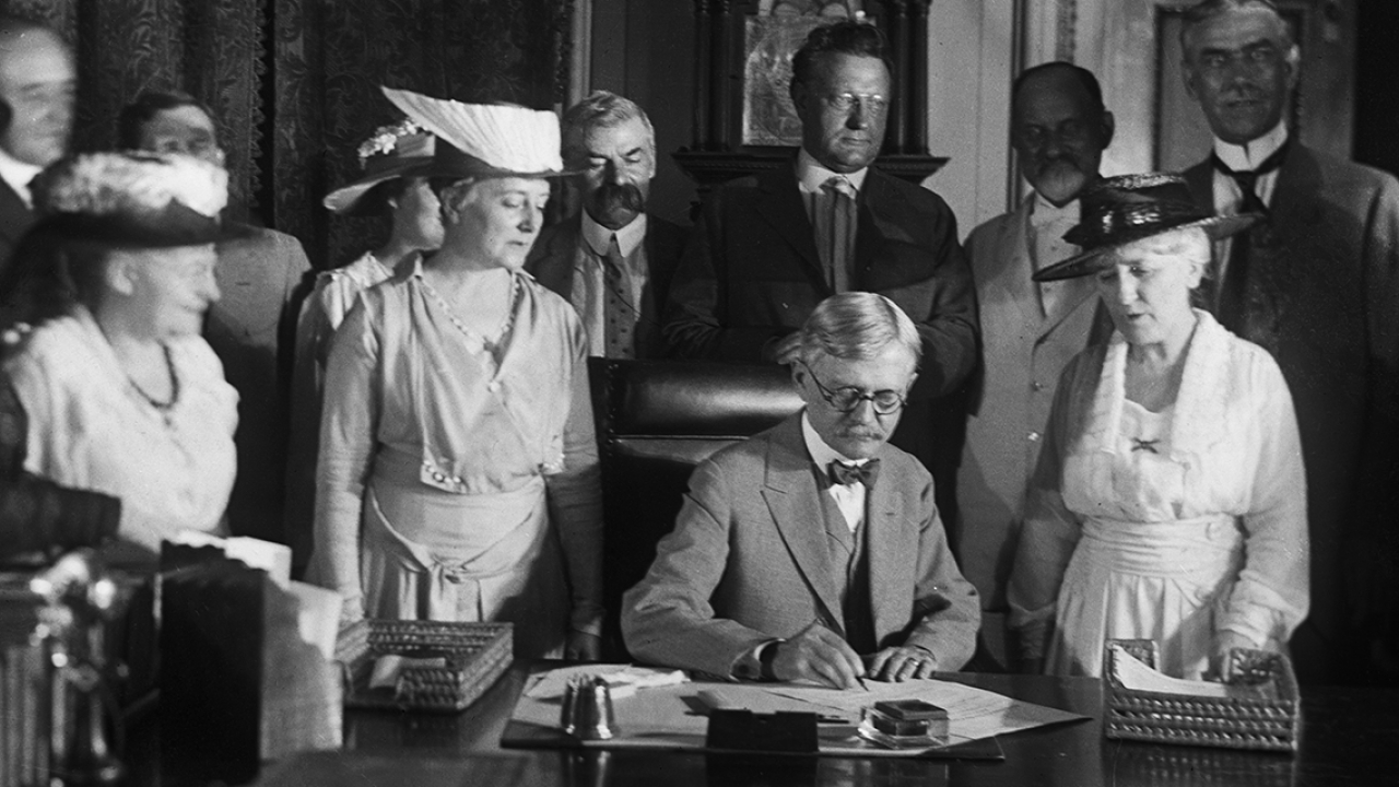 A black and white photo of a man signing a document with women standing behind him.