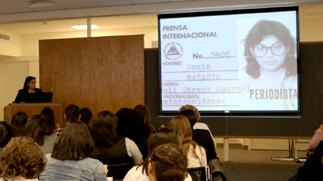 Sonia Nazario, a journalist, speaks to a room of students. On a projector there is an image of her press pass.