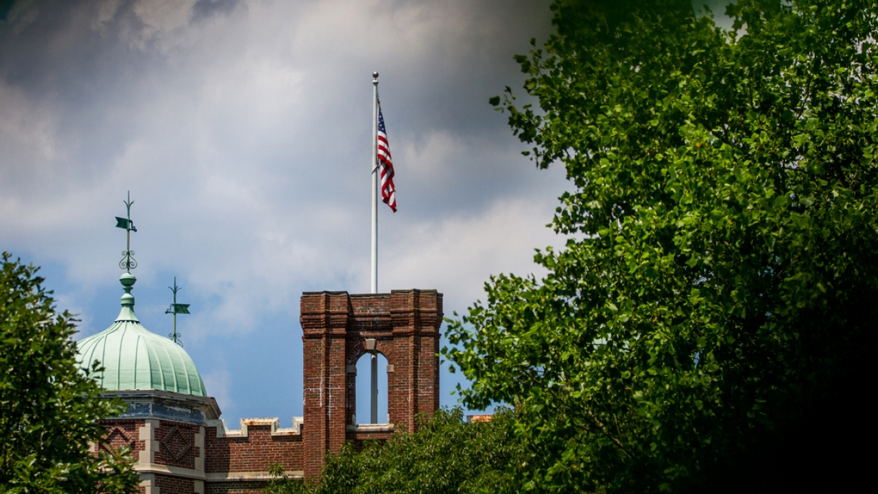 A photo of a flag on top of a residence hall.