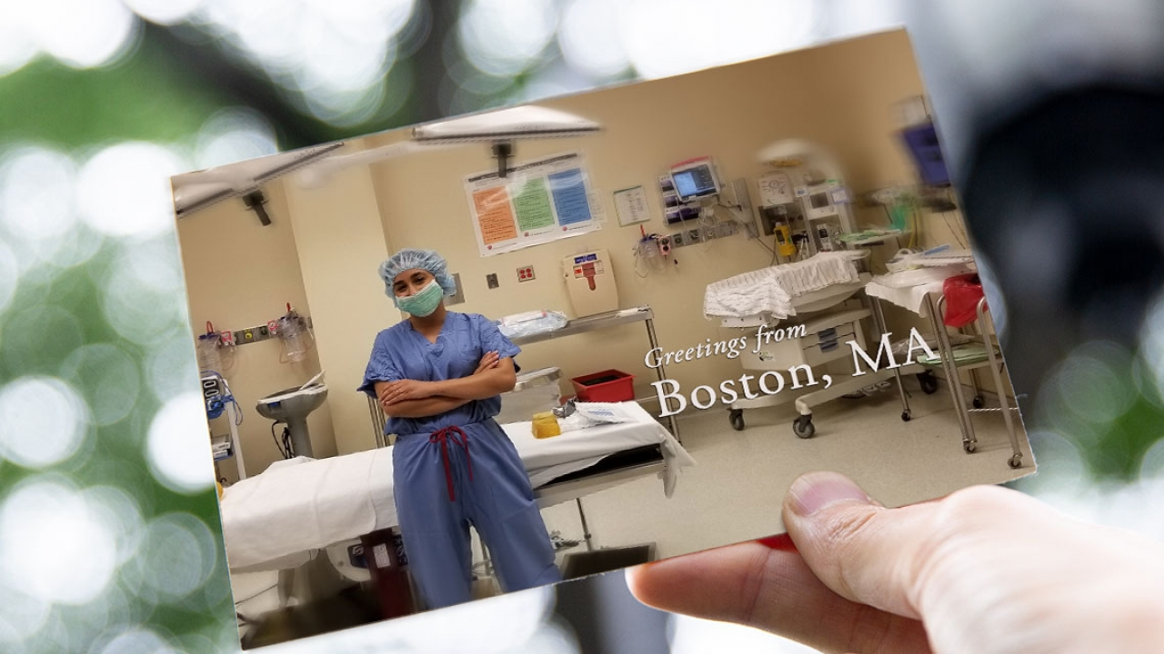 A student wearing hospital scrubs stands in front of an operating table in a hospital room