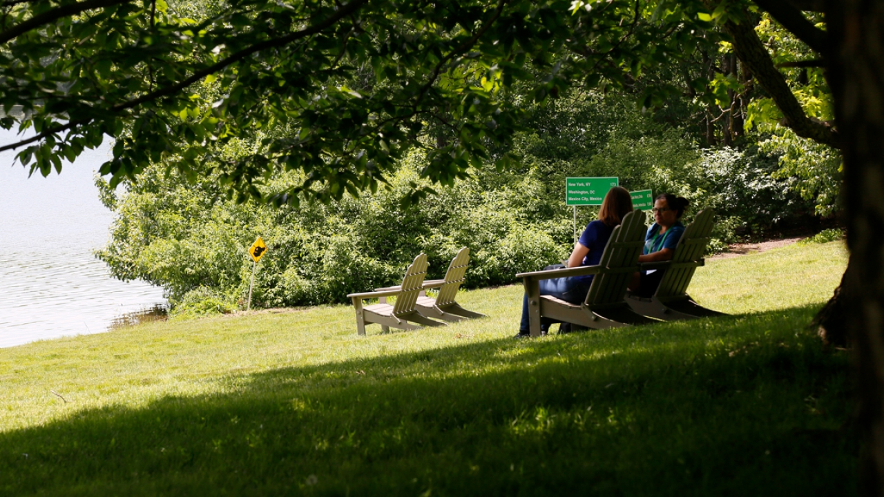 Two people sit by lake waban near signs that read the names of cities around the world.