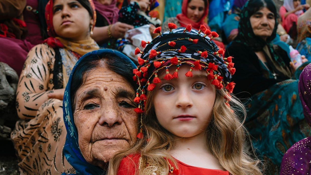 An older woman and young child look directly into the camera. They wear bright traditional kurdish clothing.