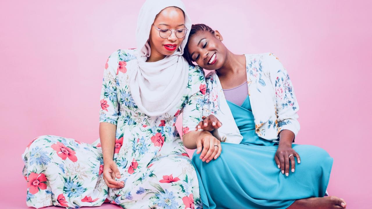 Wellesley Alumnae Makkah Ali '10 and Ikhlas Saleem '11 lean on each other.