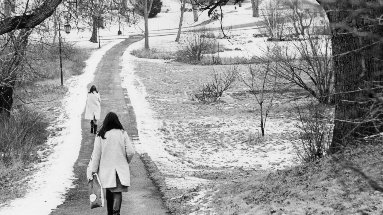 Two students walk a path at Wellesley College. There is a dusting of snow.