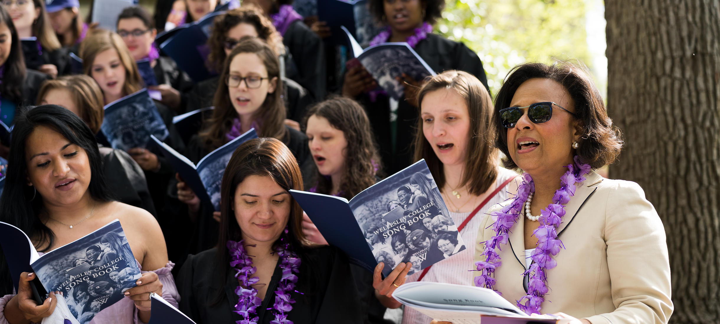 Picture of President Paula Johnson, students, singing, Wellesley College songbook.