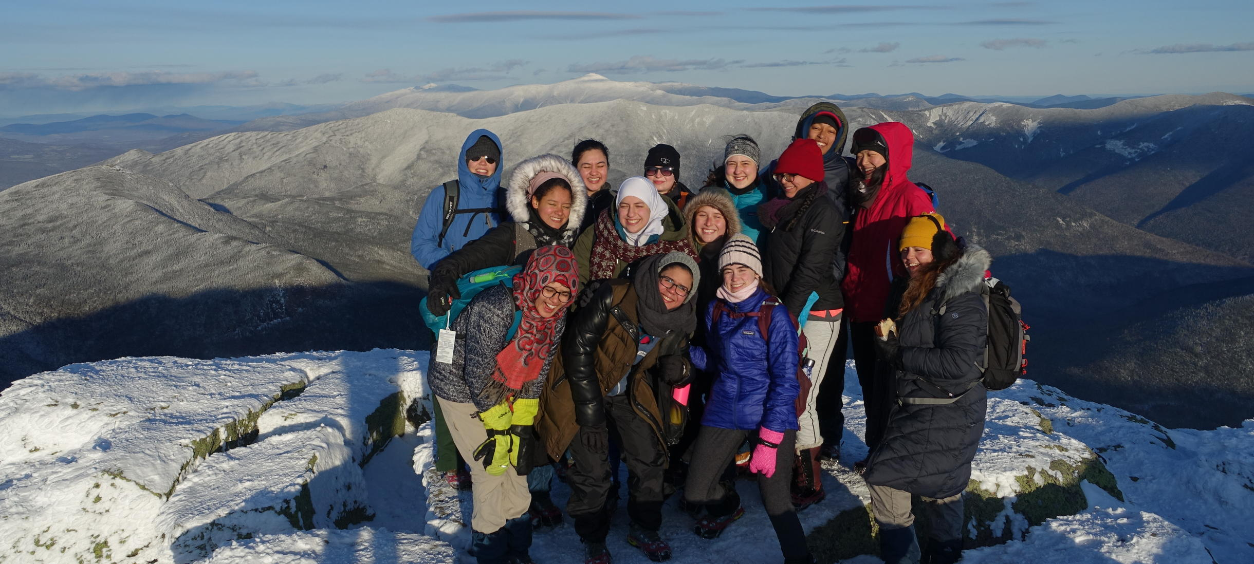 Group of students smiling on top of mountain