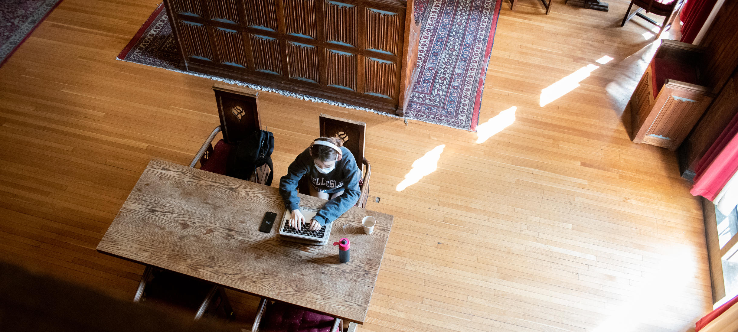 Picture of student, library, studying, oriental rugs, wood floors, sunlight.