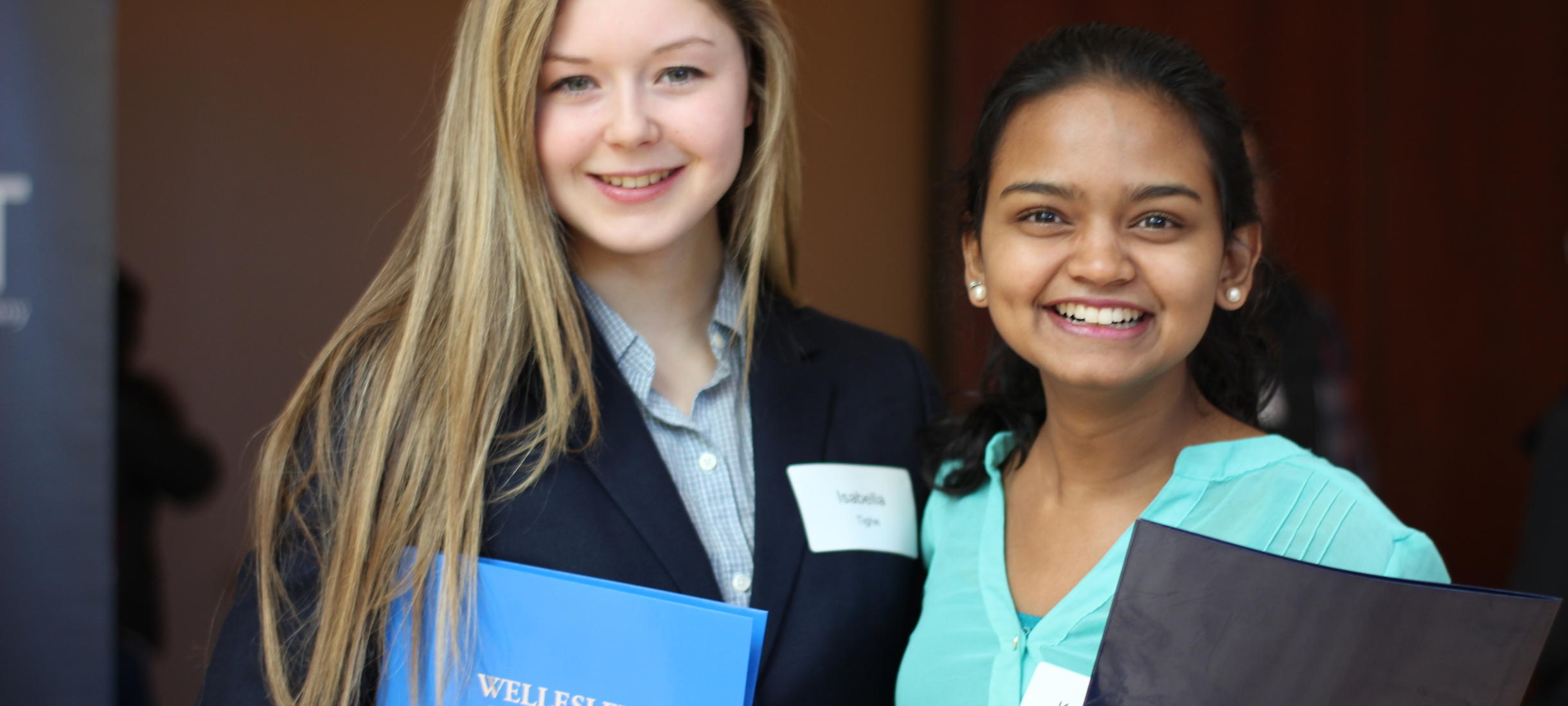Two students smiling holding Wellesley College folios
