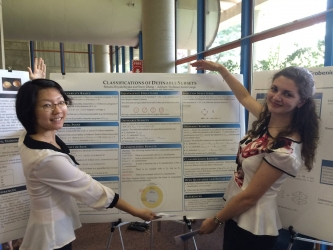 Two students show off their summer research board