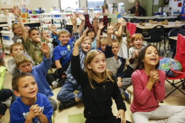 elementary students raise their hands