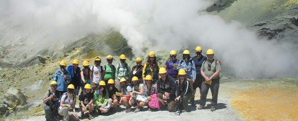 Student pose in front of steam from the White Island Volcano